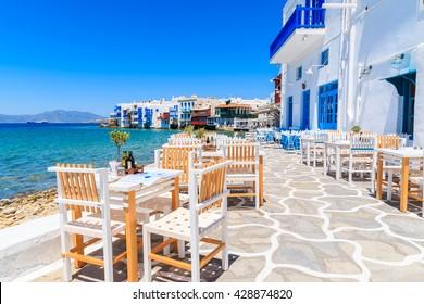 Stühle mit Tischen in typisch griechischer Taverne in Little Venice im Stadtteil Mykonos, Insel Mykonos, Griechenland