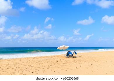 Chairs and umbrella on beach  big waves on resort island Fernando de Noronha, Brazil. Selective focus