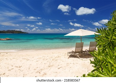 Chairs and umbrella on a beautiful tropical beach of Seychelles island