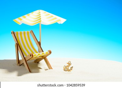 A chaise longue under an umbrella on the sandy beach, sky with copy space