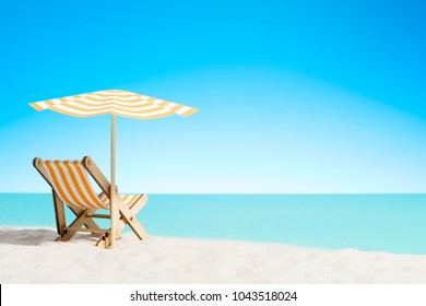 A chaise longue under an umbrella on the sandy beach by the sea and sky with copy space