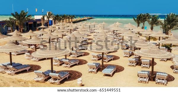 Chaise Lounge und Sonnenschirme am Strand gegen den blauen Himmel und das Meer. Ägypten, Hurghada