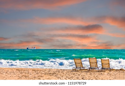 Chaise Lounges on an empty beach under cloudy skies with a freighter out to see