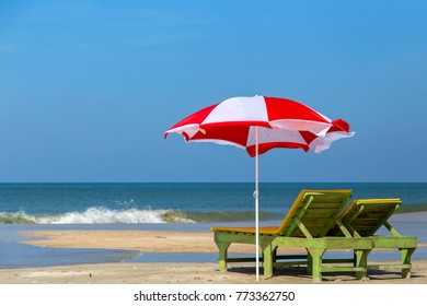 chaise lounges under a red and white umbrella on the beach of Goa.
