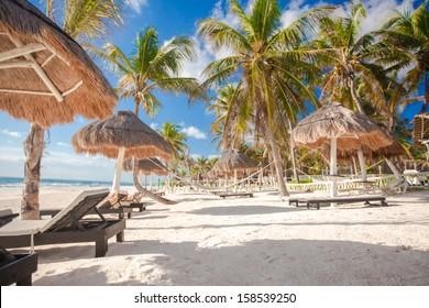 Chaise lounges under an umbrella on sandy beach