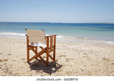 chaise on beach. landscape. water and sky.