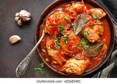 Chakhokhbili - chiken stew with cilantro (parsley) in tomato sauce in a clay bowl,traditional dish of georgian cuisine.Top view with copy space.