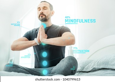 Chakra gate. Pleasant calm beardful man sitting on the bed closing eyes and meditating.