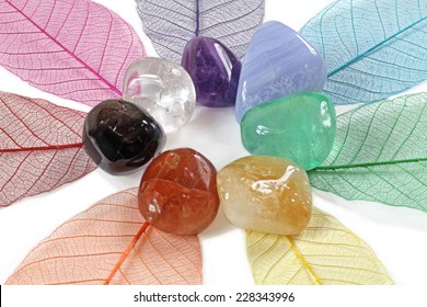 Chakra stones, close up - Chakra crystals laid on skeleton leaves forming a flower shape on white background