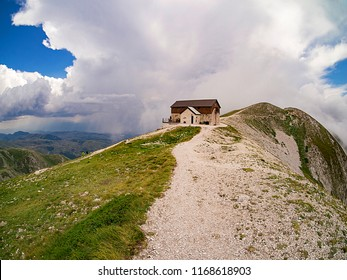 Chalet on top of the mountain. Panoramic view of a mountain retreat  on the summit of a mountain in Abruzzo, with its surrounding cliff and a threatening sky with a large picturesque cloud