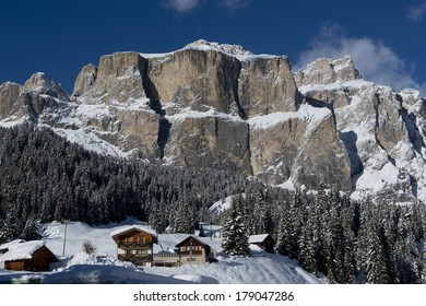 Chalet and trees under the snow in the idyllic landscape of the dolomiti in Val di Fassa