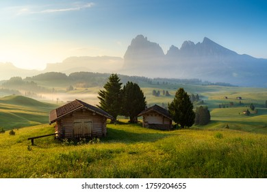Chalets at Seiser Alm, high altitude meadow with Langkofel mountain in background at sunrise, Dolomites, South Tyrol, Italy