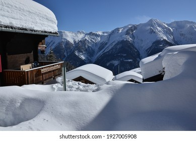 Chalets with a view under deep snow with blue skies in a ski resort