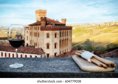 A chalice of Barolo red wine on a windowsill with breadsticks and the castle of Barolo (Piedmont, Italy) on the background