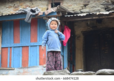 CHALISH GUAN, NEPAL – April 21, 2017 : Nepali child with blue jacket smiling to the trekking in front of stone cottage in the morning . This village is located in Ruby valley.