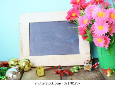 Chalk board, flower in vase and Christmas decoration