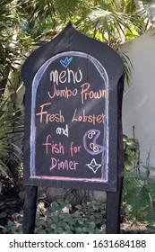 "A Chalk Board Menu that reads ""Menu Jumbo Prawn, Fresh Lobster, and fish for Dinner."""