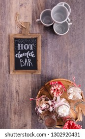 Chalk board with sign for hot chocolate bar with variety of topppings.