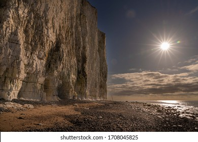 Chalk cliffs on the Sussex coast with pebble beach and sea in the foreground. Rising sun with sun bursts.