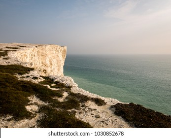 Chalk cliffs of the South Downs, East Sussex, England. Looking out into the calm waters of the English Channel from the top of the white chalk cliffs of the South Downs, England.