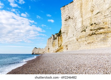 Chalk cliffs and stony coastline in Etretat, Normandy, France. Popular touristic destination