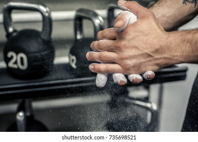 Chalk cloud with hands in gym with dumbbells