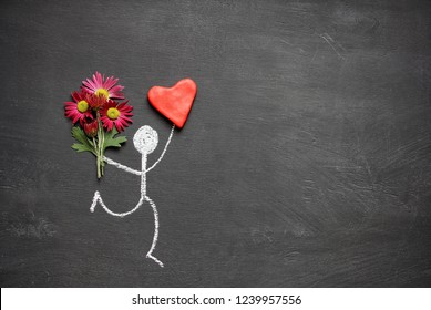 Chalk drawing man with bouquet of flowers and big red heart on chalkboard background with copy space. Valentines womens day gift or declaration of love concept.