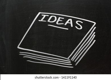 Chalk drawing on a used blackboard of a stack of paper with the word Ideas on the top page