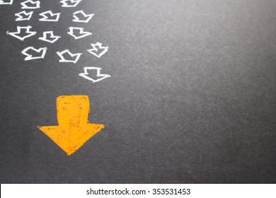 Chalk drawing of orange arrow with many white arrows as follower