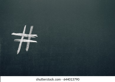 Chalk hashtag symbol on the blackboard. Copy space, horizontal orientation.