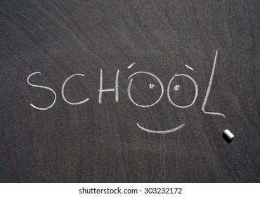 """chalk inscription """"school"""" on a blackboard"""