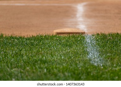 Chalk lines the field with the edge of the fresh grass and baseball base