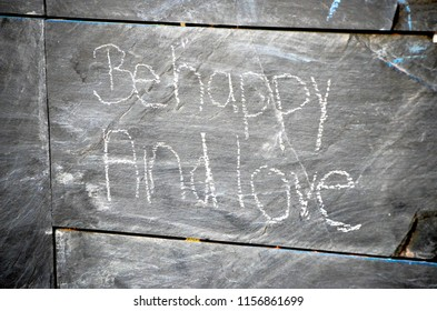 Chalk messages on a public slate wall.
