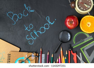 """Chalk on black chalkboard """"back to school"""" and stationary with apple and orange, Back to school concept"""