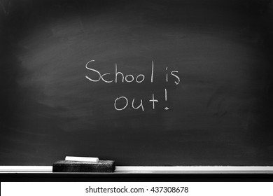Chalkboard with chalk eraser marks in white chalk School is Out Sign