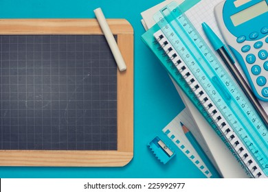 Chalkboard with chalk and stationery on light blue background, school and learning concept.
