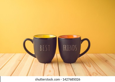 Chalkboard coffee mugs on wooden table with best friends text. Friendship day concept