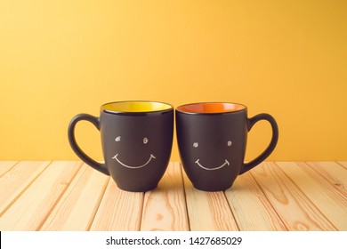 Chalkboard coffee mugs on wooden table with funny cute faces. Friendship day concept