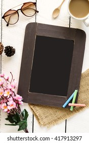 Chalkboard with cup of coffee and flower on white wooden table and copy space