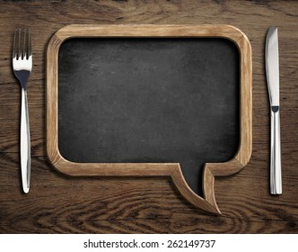 chalkboard with fork and knife on wooden dinning table