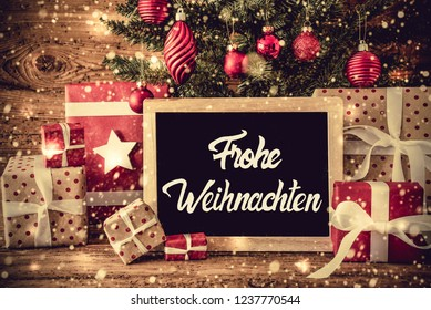 Chalkboard With German Calligraphy Frohe Weihnachten Means Merry Christmas. Christmas Tree With Christmas Tree Ball Ornament. Presents And Gifts On Rustic Wooden Background With Snowflakes