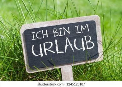 Chalkboard with the german words for i am on holiday - Ich bin im Urlaub - Shutterstock ID 1245123187
