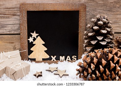 Chalkboard with gifts and wooden decoration in the snow