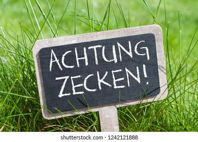 Chalkboard in the grass with the german words for Attention ticks - Achtung Zecken