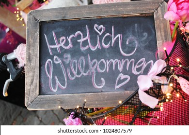 """Chalkboard with hand written words """"Herzlich willkommen"""" (German for: cordially welcome) in a decorated bicycle basket"""