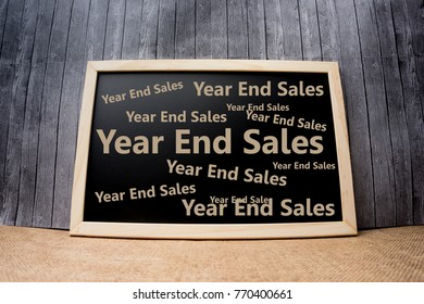 "A chalkboard on wooden table and background with word ""year end sales"""
