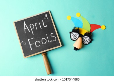 """Chalkboard with phrase """"Fool's day"""" and funny glasses on color background. 1st April celebration"""