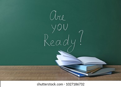 "Chalkboard with question ""Are you ready?"" and notebooks on table. Preparing for exam"