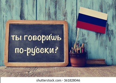 a chalkboard with the question do you speak russian? written in russian, a pot with pencils, some books and the flag of Russia, on a wooden desk