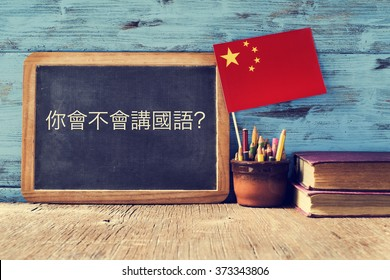 a chalkboard with the question do you speak chinese? written in chinese, a pot with pencils, some books and the flag of china, on a wooden desk